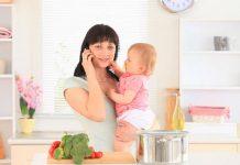 Madre multitarea: cocina, habla por teléfono mientras atiende a bebé
