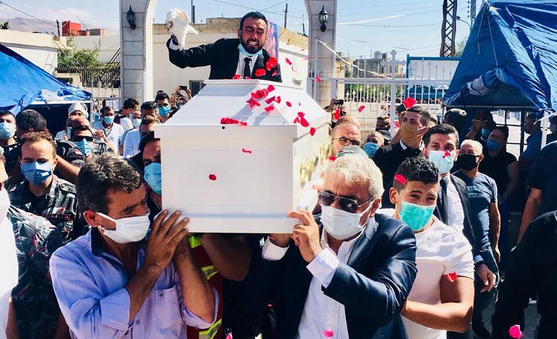 Sahar Fares's fiancé, Gilbert Karaan, waves a handkerchief over Fares's coffin at her funeral on Thursday, Aug. 4, 2020. (via The New York Times)