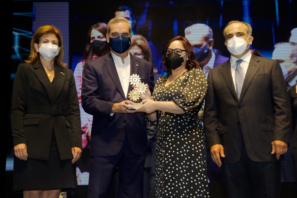 Foto 1, Elizabeth Mena recibe el galardón de Luis Abinader, Raquel Peña y Celso Marranzini.